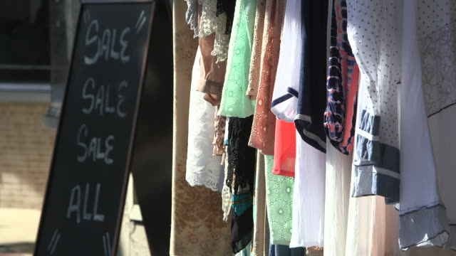 clothing on rack beside chalkboard sign - rack stock videos & royalty-free footage