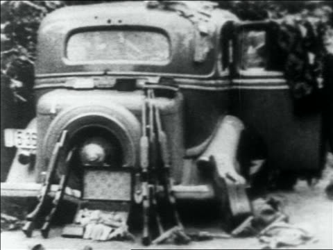 vidéos et rushes de pan clothing scattered on ground guns leaning against car / bonnie clyde's car - 1934