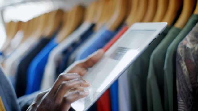 Clothing shop employee checks shirt tags and manages inventory with tablet