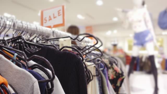 stockvideo's en b-roll-footage met kleding winkel achtergrond - kledingrek