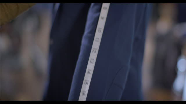 stockvideo's en b-roll-footage met clothing store clerk measures customer's sleeve length with measuring tape - herenkleding