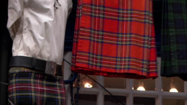 a clothing store in edinburgh displays plaid kilts. - tartan stock videos & royalty-free footage