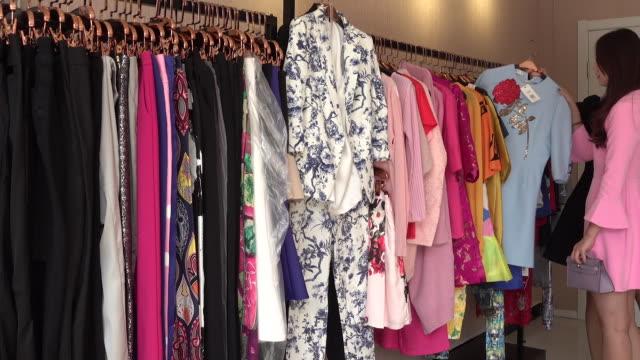 stockvideo's en b-roll-footage met clothing store owner helping customer with choosing dress - kledingrek