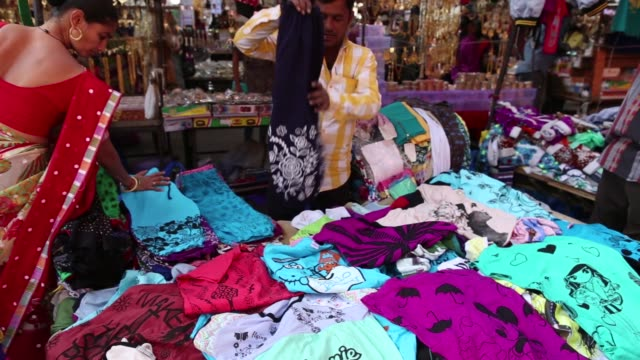 A clothing vendor displays his merchandise to passing pedestrians at a market stall in Ahmedabad Gujarat India on Wednesday Jan 11 Shoppers browse...