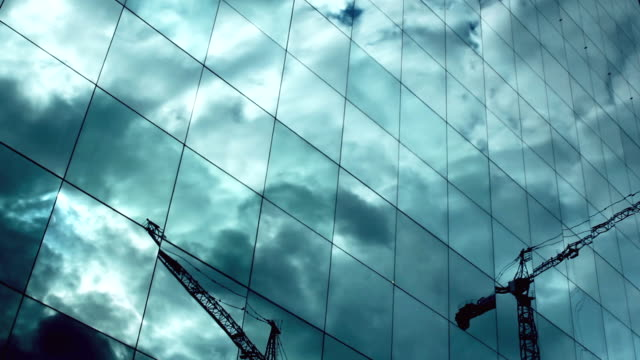 t/l cloud and industrial machine reflections on skyscraper windows - low angle view stock videos & royalty-free footage