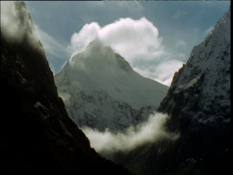 cloud billows over jagged snow capped peak, southern alps, south island, new zealand - ムラがある点の映像素材/bロール
