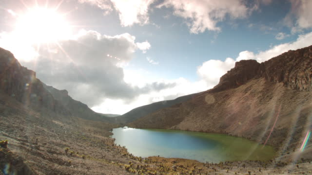 Cloud billows over mountain lake, Mount Kenya