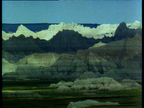 cloud cover passing over badlands of south dakota allowing sunlight to flood in - バッドランズ国立公園点の映像素材/bロール