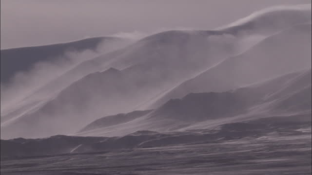 Cloud drifts over snow covered mountains, Qinghai Province, China