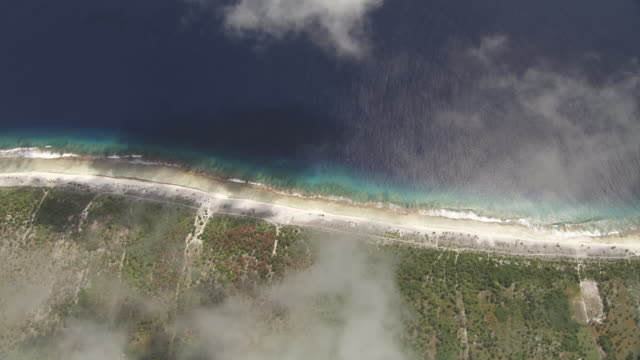 Cloud drifts over tropical coast and reef, Maupiti, French Polynesia