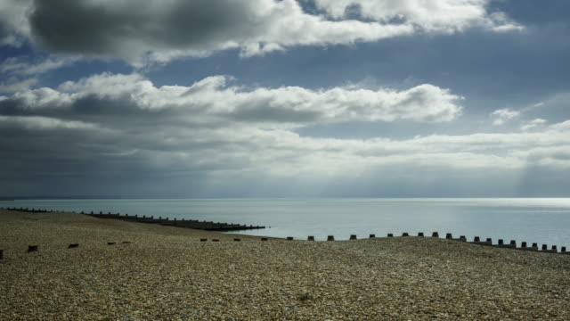 vídeos de stock e filmes b-roll de cloud is filled over a quiet pebble beach on the south coast of england in early spring - pontão