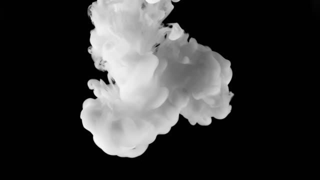 slo mo ld wolke aus weißer farbe expandiert unter wasser vor schwarzem hintergrund - dissolving stock-videos und b-roll-filmmaterial