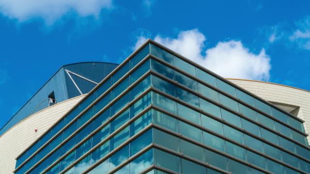 vídeos de stock e filmes b-roll de cloud reflected in glass building - exterior de edifício