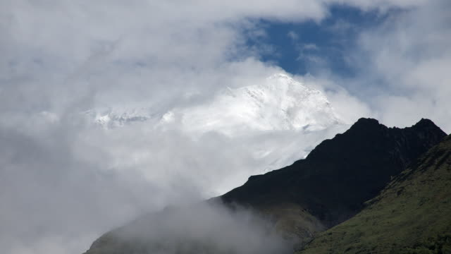 T/L cloud revealing and hiding snow-capped mountain peaks, Annapurna II, Himalayas