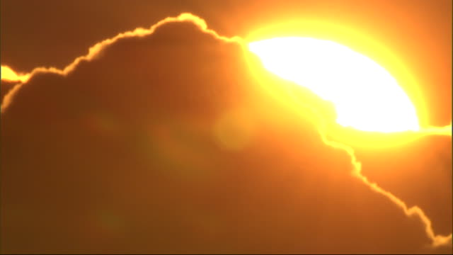 a cloud with a golden outline drifts in front of the sun. - light beam stock videos & royalty-free footage
