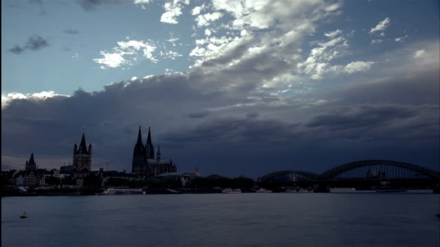 TIME LAPSE WIDE SHOT clouds above boats travel on the River Rhine with Cathedral in background at sunset , Cologne, Germany.
