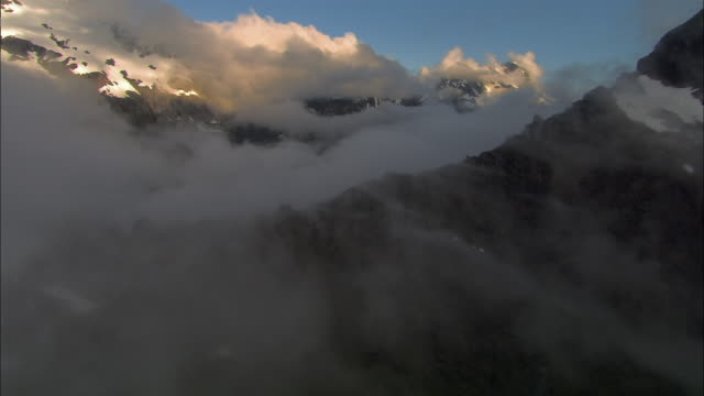 low aerial, clouds above snow capped mountains, fiordland national park, new zealand - new zealand stock videos & royalty-free footage