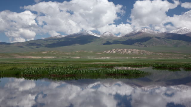 clouds and bayan har mountains reflected in lake, china - sunny stock videos & royalty-free footage