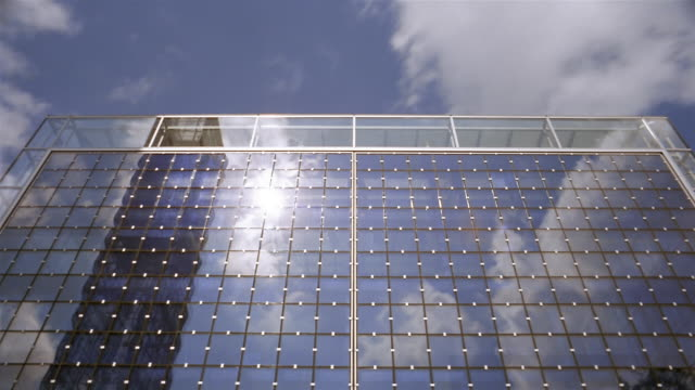 Clouds and blue sky reflect in the windows of a high-rise building.