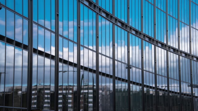 clouds and low rise office buildings are reflected in the glass of a curved facade of a modern office building with blurred street traffic moving through the form ground - gebäudefront stock-videos und b-roll-filmmaterial