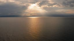 Clouds and rays of sun above the sea. Bright light with sun rays and heavy clouds above the sea. Dramatic sky