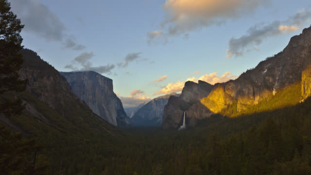 TIME LAPSE LONG WIDE SHOT clouds and shadows over pine forest covered Yosemite Valley with Bridalveil Fall and El Capitan in background in late afternoon into sunset
