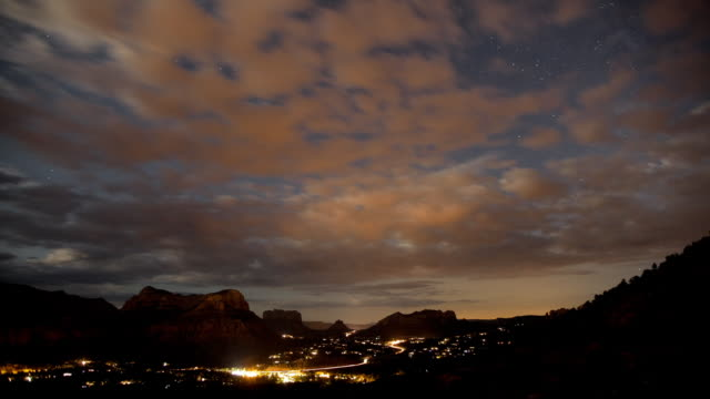 vídeos de stock, filmes e b-roll de ws t/l clouds and stars moving over city at night / sedona,  arizona, united states - sedona