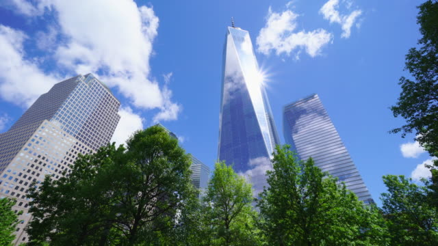 clouds are migrating above the one world trade center, which is surrounded by rows of fresh green trees at 911 memorial.the sun and clouds reflect to the one world trade center exterior wall. - ローアングル点の映像素材/bロール