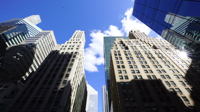 clouds are moving above the midtown manhattan skyscrapers in new york city. - 真下からの眺め点の映像素材/bロール