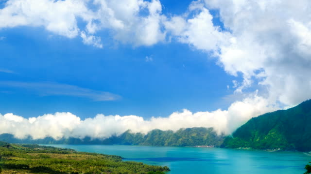 Clouds are Moving over the Peaks of the Batur Mountains and a mountain lake. Time Lapse