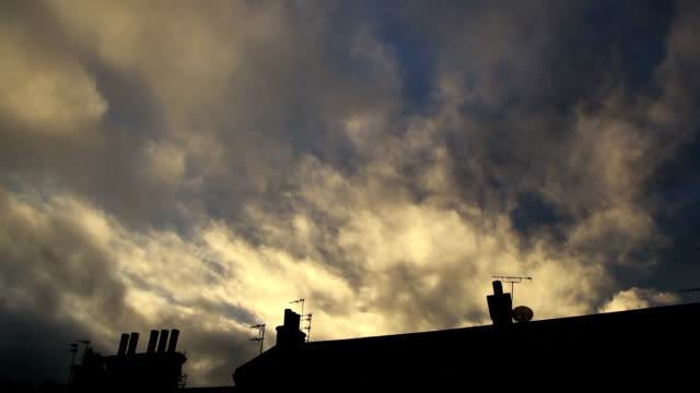 clouds at sunset blown over rooftops and chimneys - housing difficulties stock videos & royalty-free footage