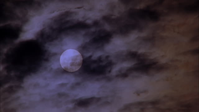 Clouds billow across night sky as full moon sets, Maui Available in HD.