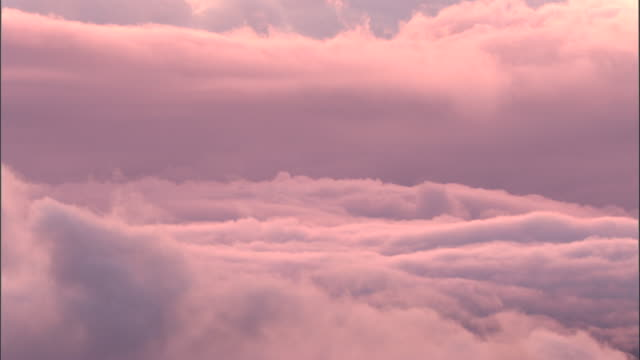 vidéos et rushes de clouds billow at sunset, papua new guinea - pink color