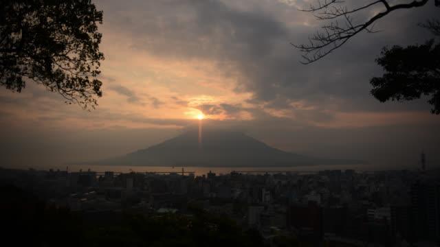 Clouds billow over Sakurajima volcano and city of Kagoshima at sunrise.