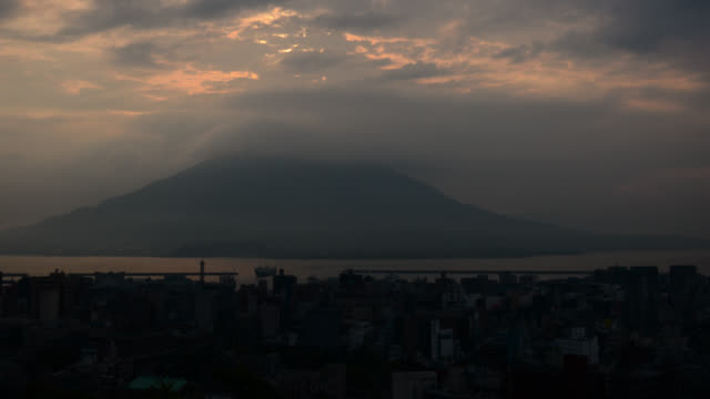 clouds billow over sakurajima volcano and city of kagoshima at sunrise. - morning stock videos & royalty-free footage