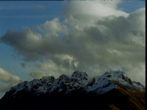 clouds billow over snow capped southern alps, south island, new zealand - ムラがある点の映像素材/bロール