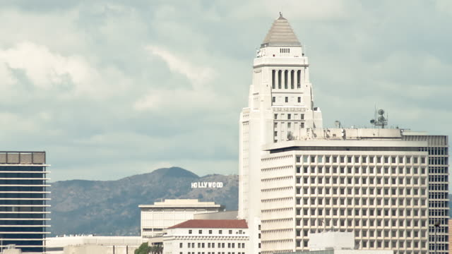 vídeos de stock, filmes e b-roll de t/l wa ls pan zo clouds billowing over city hall and the hollywood sign downtown / los angeles, california, usa - escrita ocidental