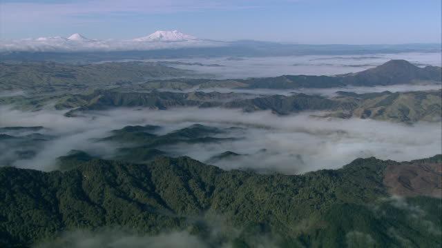 aerial clouds blanketing valleys below mountain peaks, the three volcanoes beyond / manawatu-wanganui, new zealand - tongariro national park stock videos & royalty-free footage