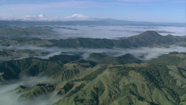 aerial clouds blanketing valleys below mountain peaks, with the three snow-covered volcanoes including mount ngauruhoe beyond / manawatu-wanganui, new zealand - tongariro national park stock videos & royalty-free footage