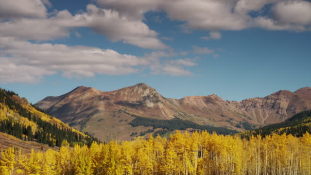 WS Clouds blowing over rocky mountains with changing aspen trees in valley during autumn / Marble City, Colorado, United States