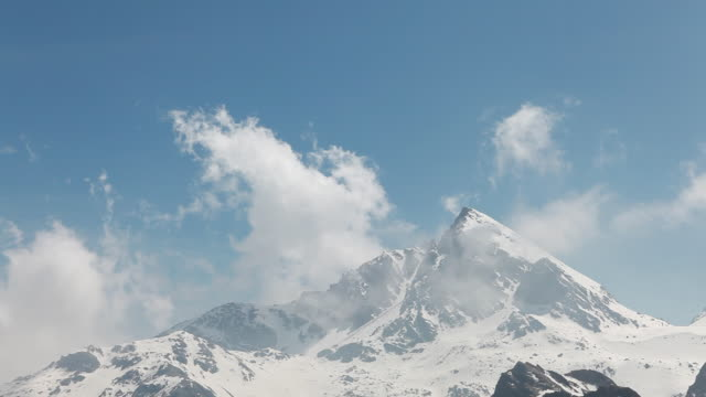T/L of clouds blowing overhead mtn peak, clearing trend