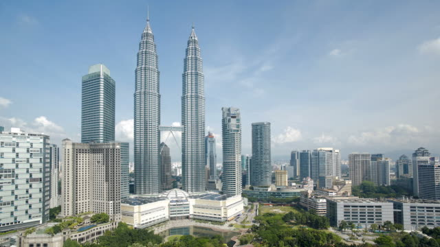 Clouds cast shadows as they drift over the Petronas Twin Towers in Kuala Lumpur's City Center.