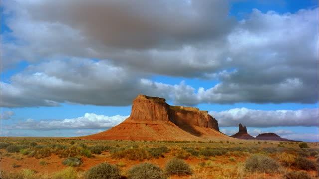vidéos et rushes de clouds cast shadows on a butte in monument valley, utah. - piton rocheux