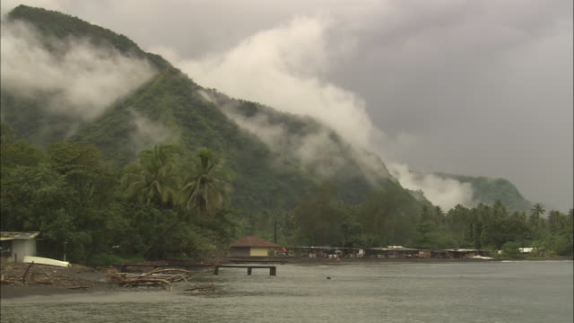 clouds cling to forested mountains on the tahiti coast. - insel tahiti stock-videos und b-roll-filmmaterial