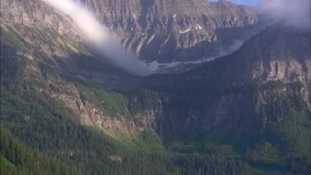 clouds cling to the peaks of mountains in glacier national park. - glacier nationalpark stock-videos und b-roll-filmmaterial