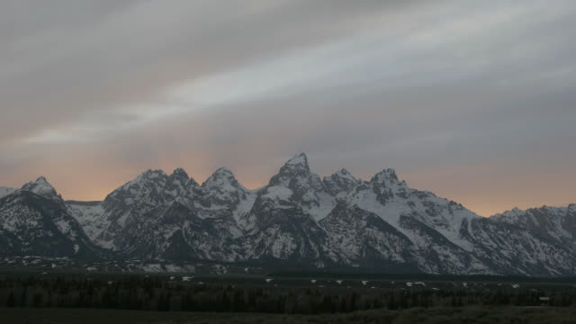 time lapse wide shot clouds, colorful sunlight, and sun rays behind snowy grand teton at sunset, wyoming - grand teton stock-videos und b-roll-filmmaterial