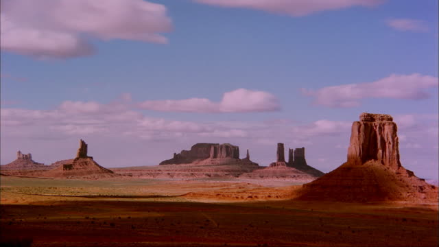 Clouds create shadows over the Monument Valley .