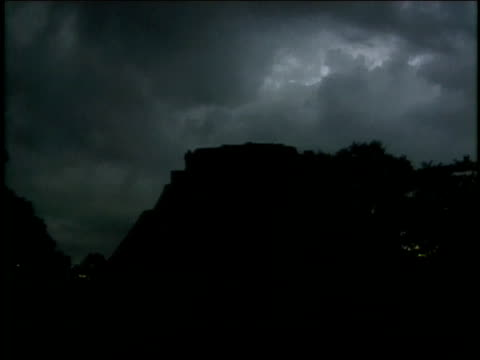 clouds darken the sky above the mayan pyramid of the magician. - puuc region stock videos and b-roll footage