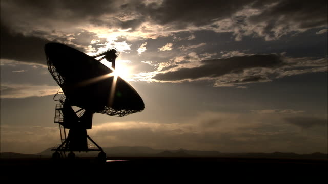 clouds drift above a radio telescope. available in hd. - sternenteleskop stock-videos und b-roll-filmmaterial
