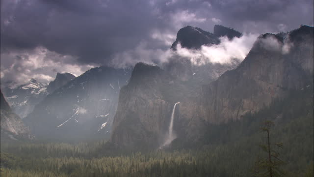 Clouds drift above a waterfall in the Yosemite National Park.